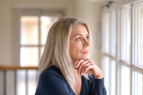 Attractive thoughtful woman with serious expression standing with her hand to her chin staring quietly out of a large window