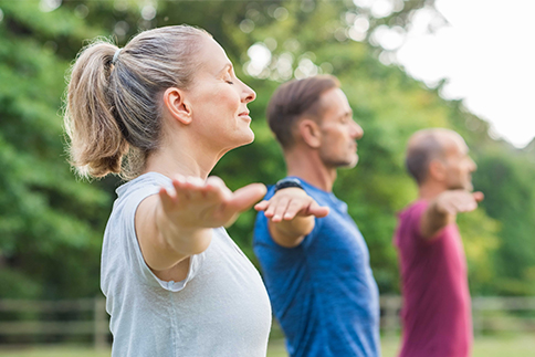 Yoga class with woman and men doing breath exercising with stretched arms.